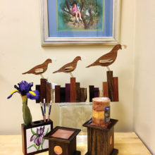 Well, Hello There is the title of the featured painting; also highlighted are a carving of three quail in a row running across a picket fence, a wooden pencil box with a ceramic tile focal piece and walnut candle holders with hammered copper inserts.