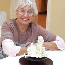 Sheila Millendorf with her sculpture Wonderland Story Teller.