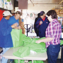 Volunteers fill holiday bags with dinner items at Agua Fria Food and Clothing Bank.