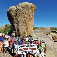 Pete Williams (Superman shirt) and 19 fellow hikers toast a unique accomplishment at Balanced Rock in the McDowell Sonoran Preserve; Photo by Lynn Warren.