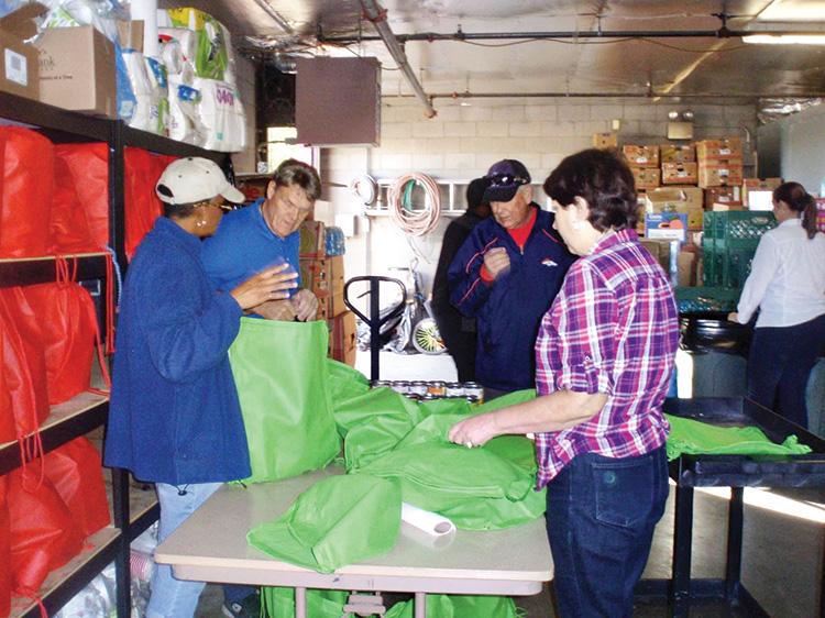PCCC volunteers filling holiday bags with dinner menu at Agua Fria Food Bank.