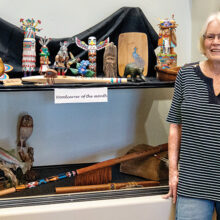 Jane with several of her carvings on the upper shelf