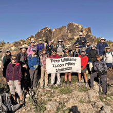 """Left to right: Charlene, Pat, Laurie, Ann, Nadine, Kathleen, Kris, Tina, Eileen, Pete, Grant, """"Ausy,"""" Diana, Dave, Ruth, Dennis, Betty, Julian, Ron, Nancy, and Pam pose on an interesting rock formation on Buckeye's Dog Bone trail."""