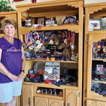 Mary Lou Furaus at home with her racquetball and pickleball trophies and medals