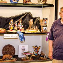 Dale with several of his carvings on the middle shelf of the display window in the Creative Arts Center.