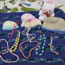 A small confession, as I was unable to break into the gallery for a current photograph of the inventory: this photo is of my very own jewelry creations and all will be available for purchase in the upcoming months. The jewelry items (pictured left to right) are a bracelet and necklace of lavender serpentine, and necklaces of cherry jade and pearl, yellow jasper, two-strands of pearl and garnet with a magnetic clasp, Brazilian fire agate also with a magnetic clasp, Amazonite, and gray pearl with metal charms. Many thanks to my hubby for the photo, but the comforter and teddy are just props and not for sale! Also included in the photo are items made for Knimble Kneedles charitable distribution, including a lapghan and chemo hats for children and teens at Banner Thunderbird and baby caps for Banner Estrella. Similar items are always available in the gallery to raise money for the club's charitable work.
