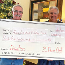 PC Dem Club President John Moore and Vice President Chuck Veltri display the mock check reflecting the club's contribution to the Agua Fria Angel Tree project.