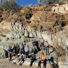 Some of the local geology. Hikers (from left to right): Art Arner, Charlene Elijew, Alex Elijew, Nancy Love, Jo Ann Talent, Mary Hill, Ron Grove, Gary Baker, hike leader Joe Clarkson, and Dave Schuldt. (Photo by Dana Thomas)