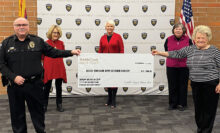 """Front row from left to right: Chief of Police Santiago """"Jimmy"""" Rodriguez and Wally Campbell; back row from left to right: Barbara Hockert, Suzanne Butler, and Charlotte Krause"""
