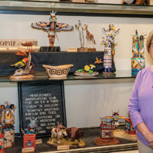 Elaine with several of her carvings on the middle shelf of the carving club's display window in the Creative Arts Center.