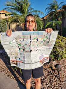 Susie Nee holding the PebbleCreek map after walking all 65 miles.