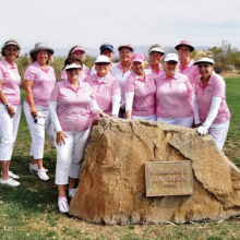The Gimme Girls Golf Group gathered in front of a rock placed in memory of the founder of the Los Caballeros Golf Club in Wickenburg. Front row (left to right): Sharon Johnson, Suzan Simons, Kathy Carney, Barb Chilton, and Sue White; Back row: Mary Barry, Judy Layton, Maria Murray, Carol Mathias, Cheryl Skummer, Lynn Grice, and Jayne Dinan